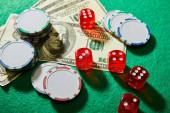 Vysokoúhlý pohled na dolarové bankovky, kostky a žetony kasina na zelené