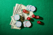 Top view of dollar banknotes, dice and casino chips on green