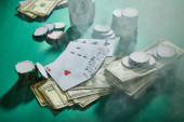 High angle view of playing cards, dollar banknotes and casino tokens with smoke around on green
