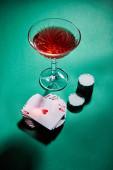 Vysoký úhel pohledu na sklo koktejlu v blízkosti hracích karet a kasinové žetony na zelené