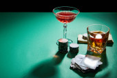 High angle view of glasses of cognac and cocktail with money, casino chips and playing cards on green surface isolated on black