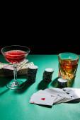 Sklenice koňaku a koktejl s penězi, žetony a hracími kartami na zeleném povrchu izolované na černém