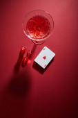 Horní pohled na sklo koktejl v blízkosti balíčku karet a kostky na červeném pozadí