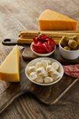 Vysoký úhel pohledu na misky s antipasto přísady v blízkosti sýra, salámové plátky a tyčinky na prknech na dřevěném pozadí