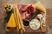 Horní pohled na tabuli s tyčinkami, sýrem, plátky salámu a antipastovými ingrediencemi na hnědé
