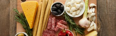 Top view of board with antipasto ingredients on wooden background, panoramic shot stock vector