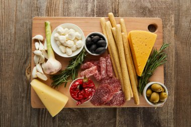 Top view of board with antipasto ingredients on wooden background stock vector