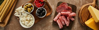 Top view of cheese, salami slices and antipasto ingredients on boards on brown background, panoramic shot stock vector