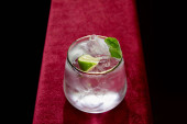Fotografie High angle view of glass with fresh mojito, mint and lime slice isolated on black