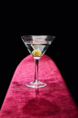 Cocktail glass with vermouth and whole olive on toothpick on pink surface isolated on black
