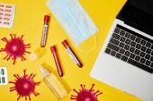 felső nézet a kémcsövek koronavírus felirattal közel orvosi maszk, buborékcsomagolás tablettákkal, üveg antibakteriális folyadék és laptop sárga