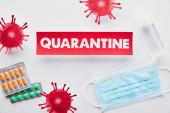 Draufsicht auf Papier mit Quarantäne-Schriftzug in der Nähe des Virus, medizinischer Maske, Pillen und Händedesinfektionsmittel auf weiß