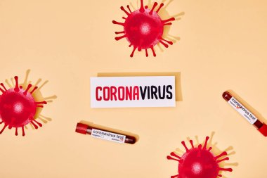 Top view of paper with coronavirus lettering near test tubes with coronavirus test and drawn virus on beige stock vector