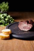 selektivní zaměření chutné šunky na palubě u petržele a bagety na dřevěném stole izolovaném na černém