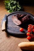 selective focus of tasty ham on board near parsley, cherry tomatoes and baguette with scattered salt and knife on wooden table