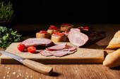 selektivní zaměření chutných šunkových plátků, cherry rajčat a nože na řezací desce u petržele a jehličí