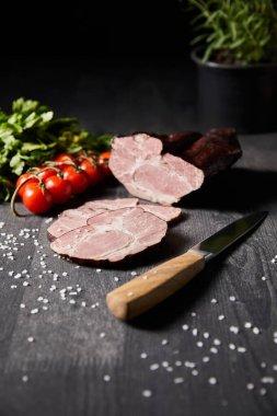 Selective focus of tasty ham sliced ham, cherry tomatoes, parsley, salt, knife on wooden grey table stock vector
