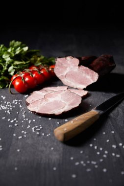 Selective focus of tasty ham sliced ham, cherry tomatoes, parsley, salt, knife on wooden grey table isolated on black stock vector