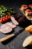 selective focus of tasty ham sliced ham, cherry tomatoes, parsley, salt, knife and baguette on wooden grey table with canape