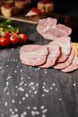 selektiver Schwerpunkt schmackhafter Schinkenscheiben, Kirschtomaten, Petersilie, Salz auf grauem Holztisch