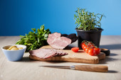 selective focus of tasty ham on cutting board with knife, parsley, cherry tomatoes, olives on wooden table on blue background