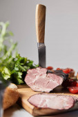 selective focus of knife in tasty ham on cutting board with parsley, cherry tomatoes and baguette isolated on grey