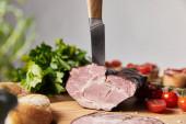 Fotografie selektiver Schwerpunkt des Messers in schmackhaftem Schinken auf Schneidebrett mit Petersilie, Kirschtomaten und Baguette isoliert auf grau
