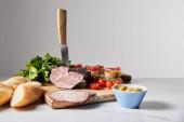 selektiver Messerfokus in schmackhaftem Schinken auf Schneidebrett mit Petersilie, Kirschtomaten, Oliven und Baguette auf weißer Oberfläche isoliert auf grau