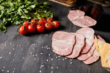 Selective focus of tasty ham sliced ham, cherry tomatoes, parsley, salt and baguette on wooden grey table stock vector