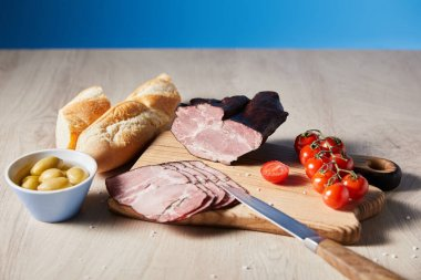 Tasty ham on cutting board with knife, cherry tomatoes, olives and baguette on wooden table on blue background stock vector