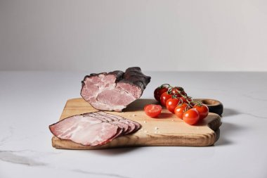 Tasty ham on cutting board with salt and cherry tomatoes on white marble surface isolated on grey stock vector