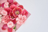 Photo top view of roses, tulips and carnations on pink and white background