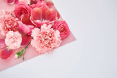 top view of roses, tulips and carnations on pink and white background