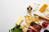 Horní pohled na masový talíř, váleček, těstoviny a ingredience na bílém pozadí