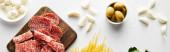 Panoramatická plodina z masového podnosu, česneku a misek s olivami a mozzarella na bílém pozadí