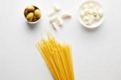 Horní pohled na špagety, česnek, mořskou sůl a misky s olivami a mozzarella na bílém pozadí