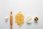Plocha ležela s česnekem, válečkem, těstovinami a miskami s olivami a mozzarellou na bílém pozadí