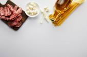 Fotografie Draufsicht auf eine Flasche Olivenöl, Fleischplatte, Knoblauch, Pasta und Schüssel mit Mozzarella auf weiß