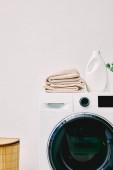mosószer palack és törölköző a mosógépen a fürdőszobai szennyeskosár közelében