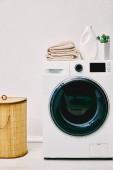 grüne Pflanze, Waschmittelflasche und Handtücher auf Waschmaschine neben Wäschekorb im Badezimmer
