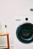 mosószer palackok a dohányzóasztalon a modern mosógép és növény közelében a fürdőszobában