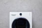 fehér mosógép közelében szürke texturált fal fürdőszobában