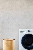 szennyes kosár közelében fehér mosógép a modern fürdőszobában