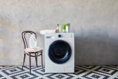 mosószer és spray palackok közelében mosógép, növények, törölközők, szék és díszszőnyeg a fürdőszobában