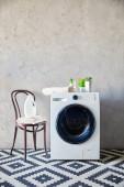 mosószer palack és törölköző a széken tányérok közelében a mosógép és díszszőnyeg a fürdőszobában