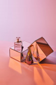 crystal transparent pyramid near perfume bottle and mirror cubes on pink background