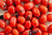 Tomaten von oben mit geschnittenen Basilikumblättern auf Backpapier