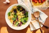 Horní pohled na misku s těstovinovým salátem v blízkosti česneku, ubrousku, špachtle a pečiva s rajčaty na dřevěném pozadí