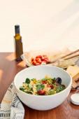 Tálak tészta saláta és só közelében palack olívaolaj, sütő edény és szalvéta fa és bézs alapon