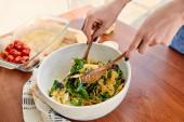 Oříznutý pohled ženy míchání těstoviny salát v misce v blízkosti ubrousek u stolu v kuchyni